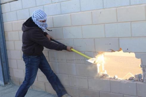 Palestinian smashes hole in the separation wall near Jerusalem.